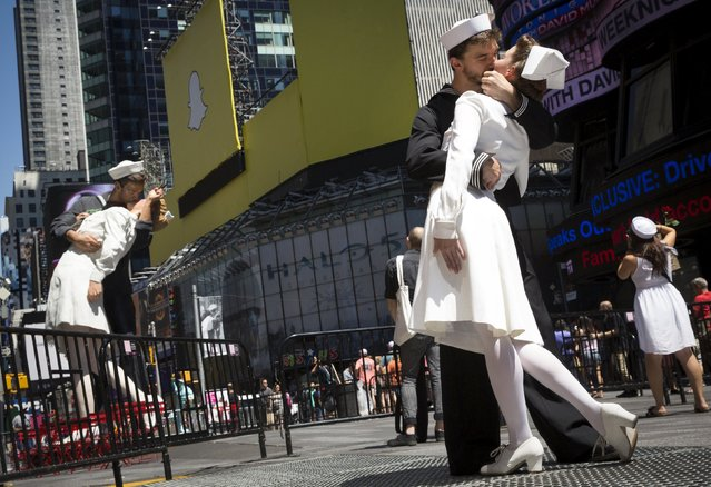 Actors reenact the famous picture of a sailor kissing a nurse on the 70th anniversary of Victory over Japan Day, near a replica sculpture in New York's Times Square August 14, 2015. The replica is being displayed to celebrate the 70th anniversary of the iconic photograph of the most famous kiss in American history that was captured between an American sailor and nurse on August 14, 1945, marking the end of World War Two. (Photo by Brendan McDermid/Reuters)