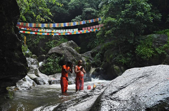 Nepali Hindu devotees pray during a walk to the Pashupatinath temple to offer prayers to Lord Shiva during Shravan festivities in Sundarijal, on the outskirts of Kathmandu on August 7, 2017. According to the Nepali calendar, Shravan is considered the holiest month of the year with each Monday of the month known as Shravan Somvar when worshippers offer prayers for a happy and prosperous life. (Photo by Prakash Mathema/AFP Photo)