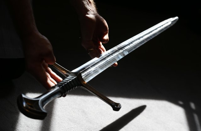 """A Bonhams employee holds """"Anduril"""" a prop sword belonging to Aragorn, hero of """"The Lord of the Rings"""" movie trilogy on July 31, 2014 in London, England. The sword, belonging to actor Sir Christopher Lee and estimated at $150,000-250,000, forms part of Bonhams """"There's No Place Like Hollywood"""" movie memorabilia auction taking place in New York on November 24, 2014. (Photo by Peter Macdiarmid/Getty Images)"""
