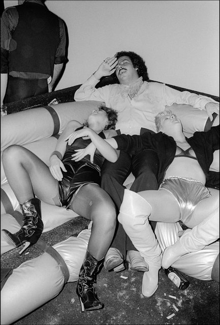At Studio 54, an unidentified trio of two woman and one man recline on a banquette, miming unconsciousness, New York, New York, September 29, 1977. (Photo by Allan Tannenbaum/Getty Images)