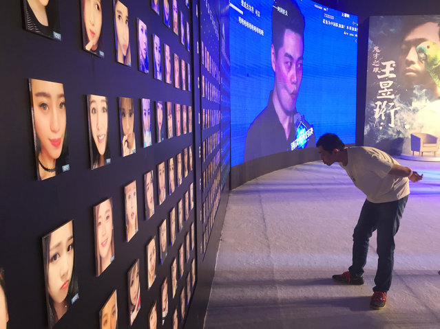 """Wang Yuheng looks at pictures of participants faces as he competes in a reality television show with """"Mark"""", an intelligent software that is able to recognize a human's face, in Hangzhou, Zhejiang Province, China June 30, 2016. (Photo by Xihao Jiang/Reuters)"""