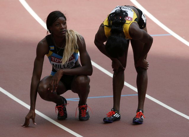 Shaunae Miller of Bahamas (L) looks at the scoreboard after the women's 400 metres heats during the 15th IAAF World Championships at the National Stadium in Beijing, China August 24, 2015. (Photo by David Gray/Reuters)