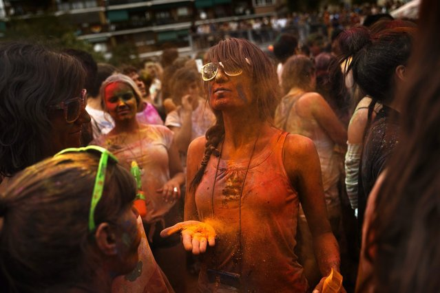 Revelers of the Holi Festival of Colors throw colored powders in the air in Madrid, Spain, Saturday, August 9, 2014. The festival is fashioned after the Hindu spring festival Holi, which is mainly celebrated in the north and east areas of India. (Photo by Daniel Ochoa de Olza/AP Photo)