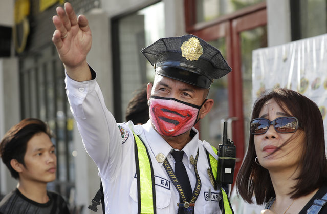 A security guard wearing a protective mask assists a woman in Manila, Philippines Friday, March 13, 2020. Many people adjusted their travel plans ahead of a government suspension of domestic travel to and from metropolitan Manila. Philippine President Rodrigo Duterte also authorized sweeping quarantines in the crowded capital to fight the new coronavirus. For most people, the new coronavirus causes only mild or moderate symptoms. For some it can cause more severe illness. (Photo by Aaron Favila/AP Photo)