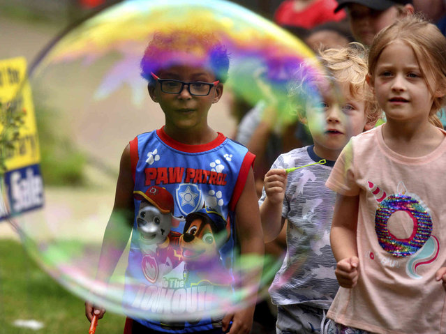 Quinn Dante, 4, Owen Miller 3, and Aria Miller 5 watch as a giant bubble floats their way at the Osterhout Free Library kids day on Wednesday June 19, 2019, in Wilkes-Barre, Pa. (Photo by Aimee Dilger/The Times Leader via AP Photo)