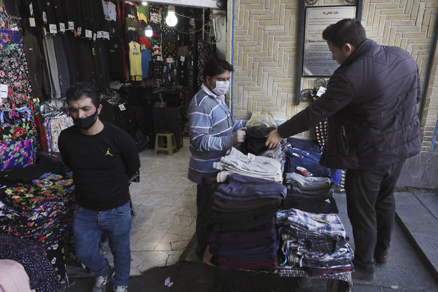 In this Tuesday, March 17, 2020, photo, a shopkeeper, center, wearing a face mask and gloves, to help protect against the new coronavirus, talks with his customer at the Tehran's Grand Bazaar, Iran. The new coronavirus ravaging Iran is cutting into celebrations marking the Persian New Year, known as Nowruz. (Photo by Vahid Salemi/AP Photo)