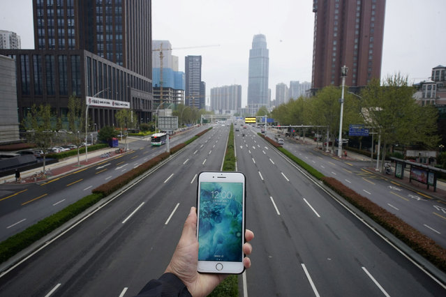 A mobile phone showing the time at noon, is displayed for a photo in front of an almost empty road with low traffic, during the coronavirus disease (COVID-19) outbreak, in Wuhan, Hubei province, China, March 31, 2020. (Photo by Aly Song/Reuters)