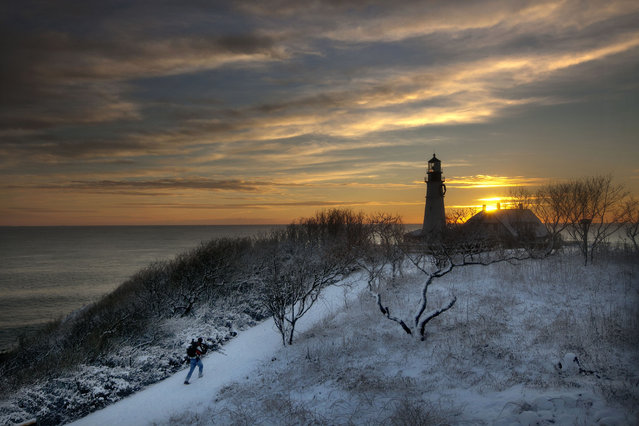 Clearing skies await a tripod-toting photographer looking for a spot to capture the early-morning light at Portland Head Light, Thursday, January 17, 2013, in Cape Elizabeth, Maine. (Photo by Robert F. Bukaty/AP Photo)