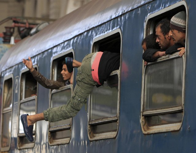 A migrant gets into a train through a window at the Keleti train station in Budapest, Hungary, September 3, 2015 as Hungarian police withdrew from the gates after two days of blocking their entry. (Photo by Bernadett Szabo/Reuters)