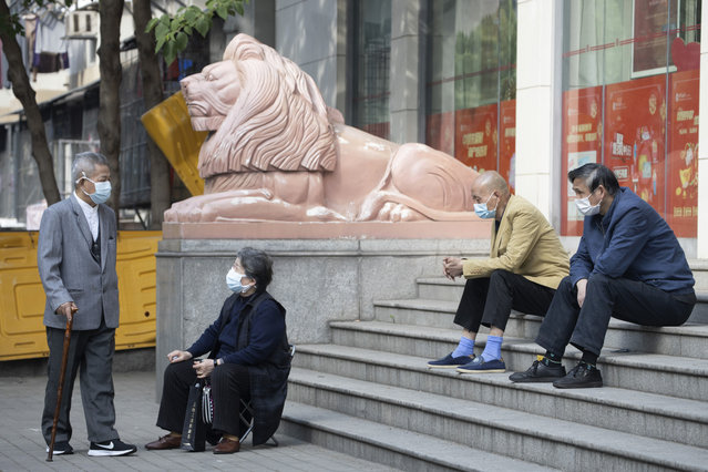 Elderly residents wearing masks against the coronavirus wait outside a bank in Wuhan in central China's Hubei province Thursday, April 16, 2020. (Photo by Ng Han Guan/AP Photo)