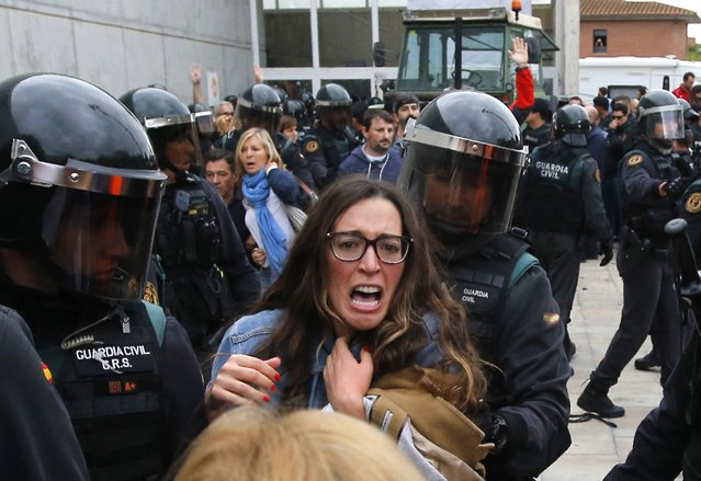 People clash with Spanish Guardia Civil guards outside a polling station in Sant Julia de Ramis, where Catalan president was supposed to vote, on October 1, 2017, on the day of a referendum on independence for Catalonia banned by Madrid. (Photo by Raymond Roig/AFP Photo)