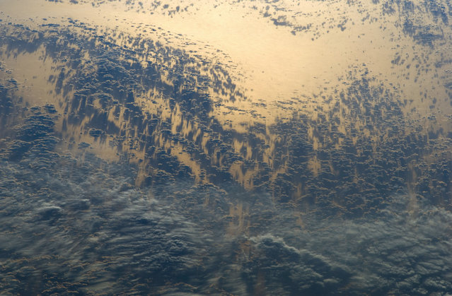 The setting sun highlights cloud patterns – as well as the Pacific Ocean surface itself – in this photograph taken by an astronaut aboard the International Space Station, on May 15, 2012. The ISS was located over the Andes Mountains of central Chile at the time. The camera view is looking back towards the Pacific Ocean as the Sun was setting in the west. (Photo by NASA)