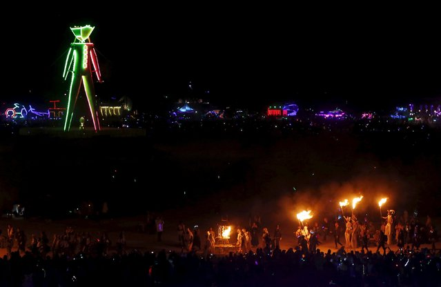 """The Fire Conclave circles the Man during the Burning Man 2015 """"Carnival of Mirrors"""" arts and music festival in the Black Rock Desert of Nevada September 5, 2015. (Photo by Jim Urquhart/Reuters)"""
