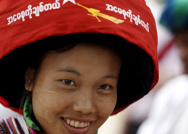 """An ethnic Lisu woman with traditional headgear waits for Myanmar pro-democracy leader Aung San Suu Kyi to arrive to give a speech on voter education at the Hsiseng township in Shan state, Myanmar September 5, 2015. The words on the cloth read, """"I love mother Suu"""". (Photo by Soe Zeya Tun/Reuters)"""