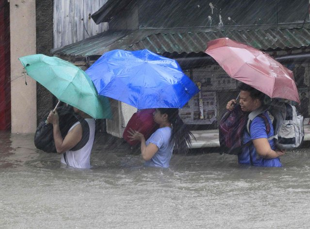 People carry their belongings as they wade through a flooded street after tropical storm Fung-Wong battered metro Manila September 19, 2014. (Photo by Erik De Castro/Reuters)