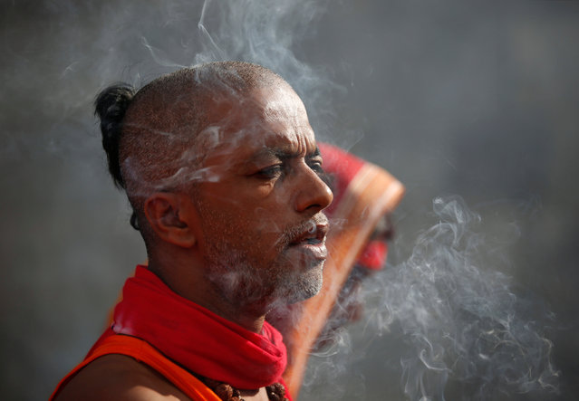 "Smoke rises from the incense as a devotee offers prayer after completing his ""Bol Bom"" (Say Shiva) pilgrimage in Kathmandu, Nepal, August 8, 2016. (Photo by Navesh Chitrakar/Reuters)"