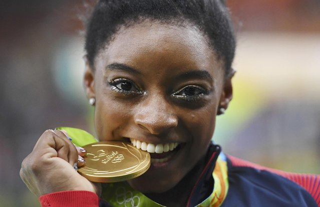2016 Rio Olympics, Artistic Gymnastics, Victory Ceremony, Women's Individual All-Around Victory Ceremony, Rio Olympic Arena, Rio de Janeiro, Brazil on August 11, 2016. Simone Biles (USA) of USA bites her gold medal on the podium after winning the women's individual all-around final. (Photo by Dylan Martinez/Reuters)