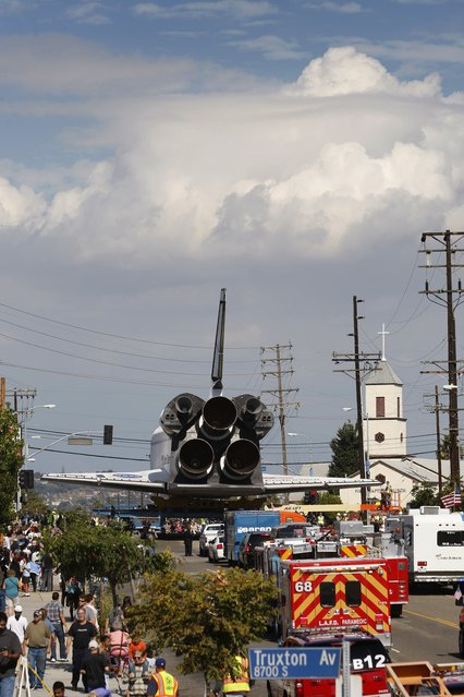 The space shuttle Endeavour approaches the intersection of La Tijera Boulevard and Manchester Avenue as it is transported to the California Science Center in Exposition Park from Los Angeles International Airport (LAX) on October 12, 2012 in Los Angeles, California. Endeavour was flown cross-country atop NASA's Shuttle Carrier Aircraft from Kennedy Space Center in Florida to LAX on its last flight ever on September 21. From there, it was transported to the California Science Center in Exposition Park where it will be on permanent public display. Completed in 1991, Endeavour was built to replace the space shuttle Challenger which disintegrated during a catastrophic re-entry accident. This fifth and final space shuttle orbiter circled the earth 4,671 times and traveled nearly 123 million miles during its 25 missions from 1992 to 2011. (Photo by David McNew)