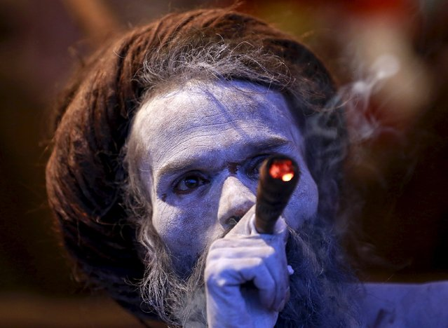 "A Naga Sadhu, or Hindu holy man, smokes inside his tent during the second ""Shahi Snan"" (grand bath) at ""Kumbh Mela"", or Pitcher Festival, in Trimbakeshwar, India, September 13, 2015. (Photo by Danish Siddiqui/Reuters)"