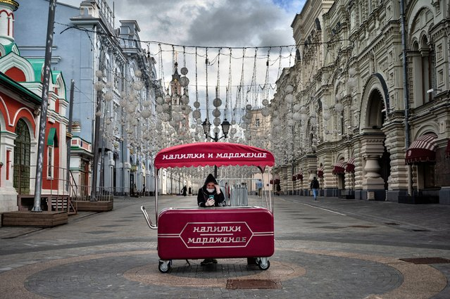 A woman wearing a protective face mask sells ice cream in downtown Moscow on June 4, 2020. The World Health Organisation said on June 3 the number of coronavirus cases was slowly declining in Russia as the Kremlin prepared to stage a vote to change the constitution. (Photo by Dimitar Dilkoff/AFP Photo)