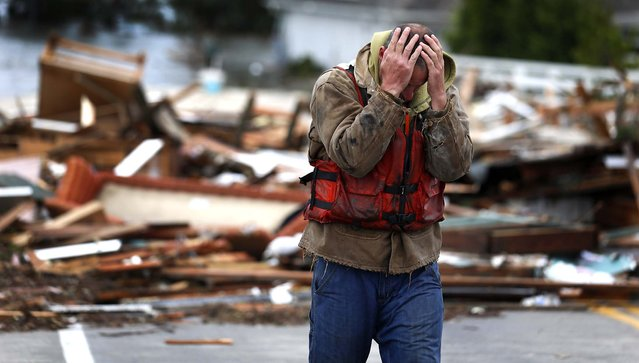 Brian Hajeski, 41, of Brick, N.J., reacts after looking at debris of a home that washed up on to the Mantoloking Bridge Mantoloking, N.J. (Photo by Julio Cortez/Associated Press)