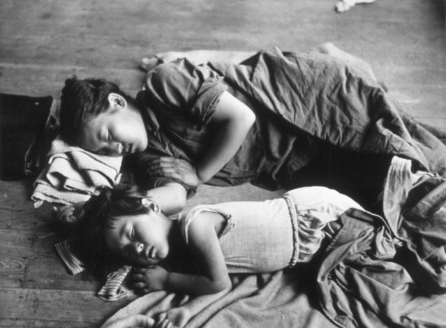 A South Korean mother and her child sleeping on the floor of a schoolroom in Taejon. 1950. (Photo by Haywood Magee/Getty Images)