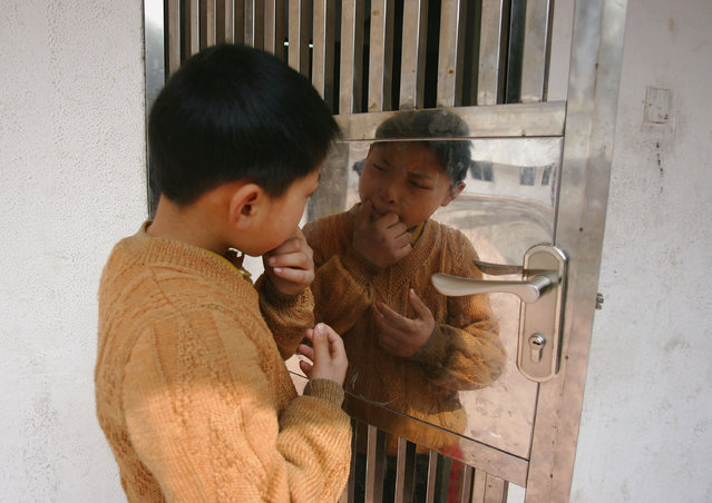 A kid from Sichuan provice looks at his reflection in a door at an assistance center February 23, 2005 in Shenzhen, Guangdong Province, China. (Photo by Cancan Chu/Getty Images)