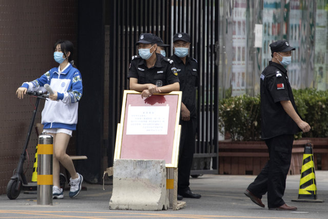 A student walks by security guard as she leaves from a school after classes were cancelled in Beijing on Wednesday, June 17, 2020. On Wednesday, the city of 20 million people raised its threat level from 3 to 2, leading to the cancellation of classes, suspended reopenings and stronger requirements for social distancing. (Photo by Ng Han Guan/AP Photo)