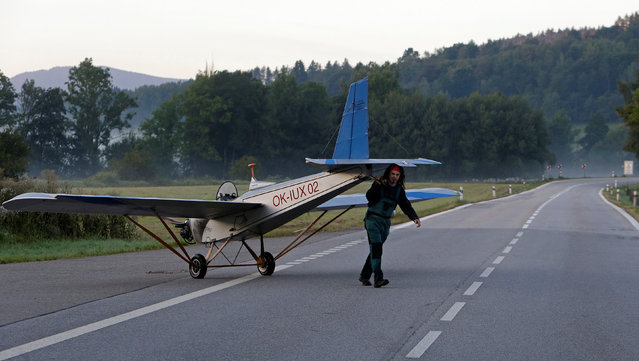 Aviator Frantisek Hadrava pulls Vampira, an ultralight plane based on the U.S.-design of light planes called Mini-Max, across a road near the town of Ckyne, Czech Republic, August 24, 2016. (Photo by David W. Cerny/Reuters)