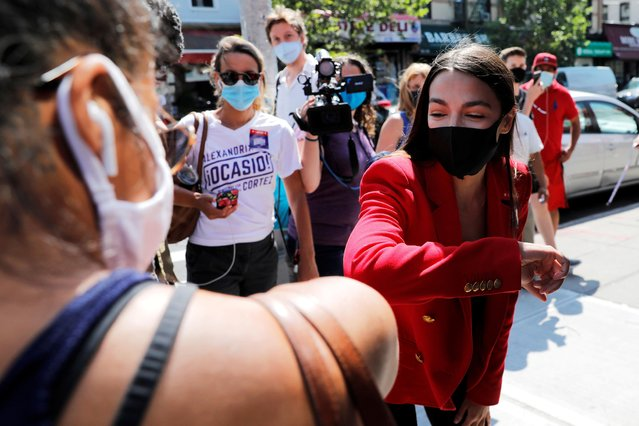 U.S. Rep. Alexandria Ocasio-Cortez (D-NY) bumps elbows with local resident Upkar Chana while greeting voters during the Democratic congressional primary election in the Queens borough of New York City, New York, U.S., June 23, 2020. (Photo by Mike Segar/Reuters)