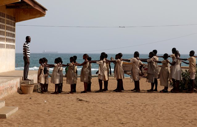 Pupils line up in the yard of their school, which, according to head teacher Hlongnoin Akouavi, was damaged by sea storms and is under threat from coastal erosion, in Baguida, a suburb of Lome, Togo, February 24, 2020. (Photo by Luc Gnago/Reuters)