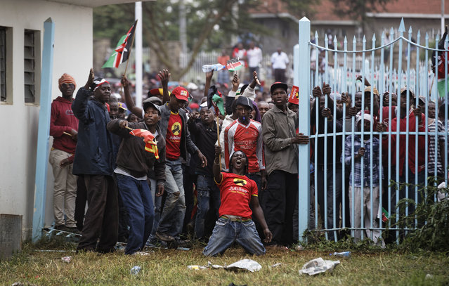 Supporters of President Uhuru Kenyatta engage in rock-throwing clashes with police at his inauguration ceremony after trying to storm through gates to get in and being tear-gassed, at Kasarani stadium in Nairobi, Kenya Tuesday, November 28, 2017. (Photo by Ben Curtis/AP Photo)