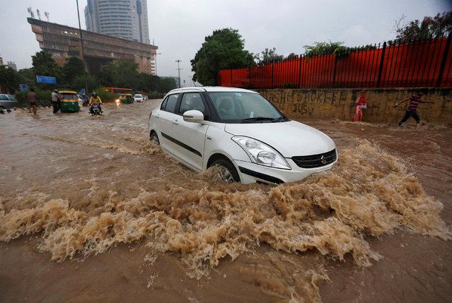 A car drives through a flooded street during heavy rains in New Delhi, India, August 29, 2016. (Photo by Adnan Abidi/Reuters)