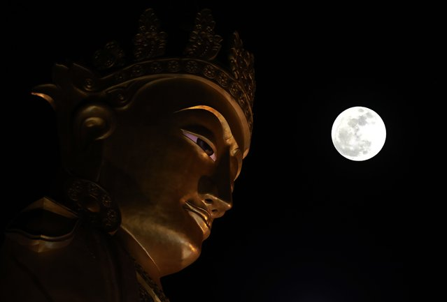 "A multiple exposure image shows a so-called ""Supermoon"" near the Buddha statue in Yangon, Myanmar, 03 December 2017. (Photo by Nyein Chan Naing/EPA/EFE)"