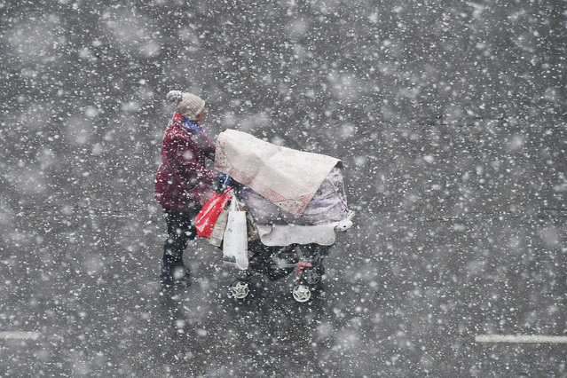 A woman pushing a stroller walks in the snow in Yantai, Shandong province, China December 4, 2017. (Photo by Reuters/China Daily)