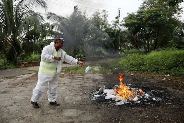 A man, who attends the burial of a man who died due to the coronavirus disease (COVID-19), burns his protective suits, in Dhaka, Bangladesh, June 8, 2020. (Photo by Mohammad Ponir Hossain/Reuters)