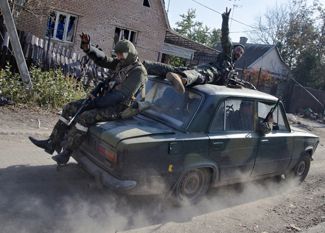 Pro-Russian rebels ride atop a car to their positions not far from the Donetsk Sergey Prokofiev International Airport in the city of Donetsk, eastern Ukraine, Tuesday, October 14, 2014. (Photo by Dmitry Lovetsky/AP Photo)