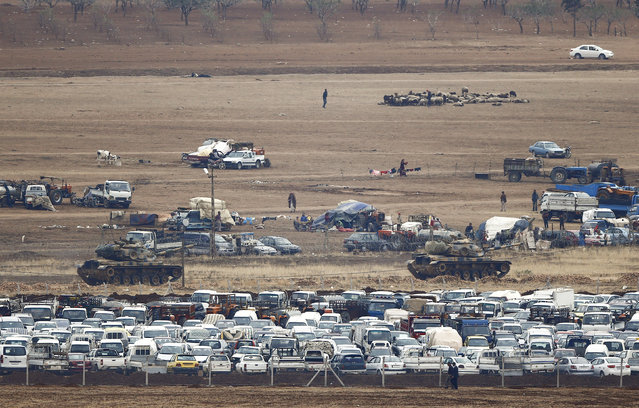 "Turkish army tanks pass abandoned cars of Kurdish Syrian refugees near ""no-man's land"" at the Mursitpinar border crossing on the Turkish-Syrian border in the southeastern town of Suruc in Sanliurfa province on October 17, 2014. (Photo by Kai Pfaffenbach/Reuters)"