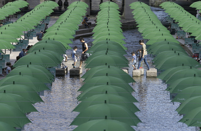 Visitors walk under umbrellas on display over Cheonggye stream during a campaign to raise donations to help underprivileged children in Seoul, South Korea, Tuesday, September 29, 2015. (Photo by Ahn Young-joon/AP Photo)