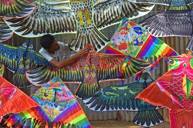 A vendor adjusts kites for sale as he waits for customers along the roadside in Dhaka on July 8, 2020. (Photo by Munir Uz Zaman/AFP Photo)