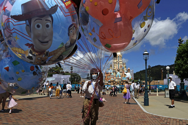 An employee wearing a face mask to prevent the spread of the new coronavirus, sells balloons at the Hong Kong Disneyland Thursday, June 18, 2020. In March, Hong Kong closed its borders to overseas countries, restricting visitors to those who have spent more than 14 days in mainland China, Macao and Taiwan. Tourist numbers plunged nearly 90%, with only about 3.5 million visitors arriving in the city between January and June this year. The city's airlines, hospitality and tourist industries – which had already took a hit from months of anti-government protests last year – took a second beating, with the government pledging $51.6 million in subsidies to help them stay afloat. (Photo by Kin Cheung/AP Photo)