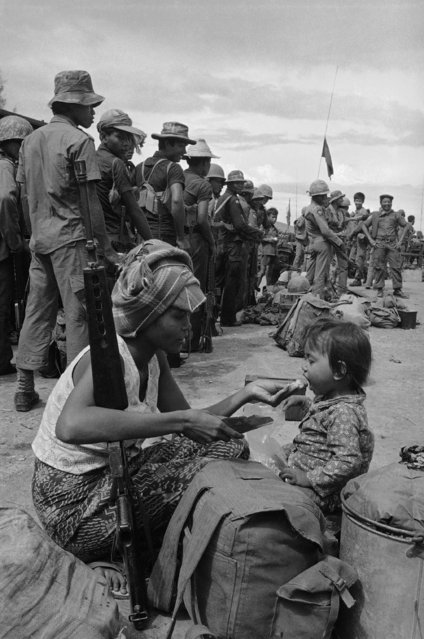 The wife of a Cambodian government soldier feeds her daughter a ball of rice as they come to say goodbye as his unit heads out on an operation to retake positions lost to Khmer Rouge insurgents near the province capital of Kampong Chhnang north of Phnom Penh, October 1, 1974. In Cambodia, families often live with the soldiers, especially in static positions such as base camps and outposts, but do not accompany them on actual operations. (Photo by Tea Kim Heang aka Moonface/AP Photo)