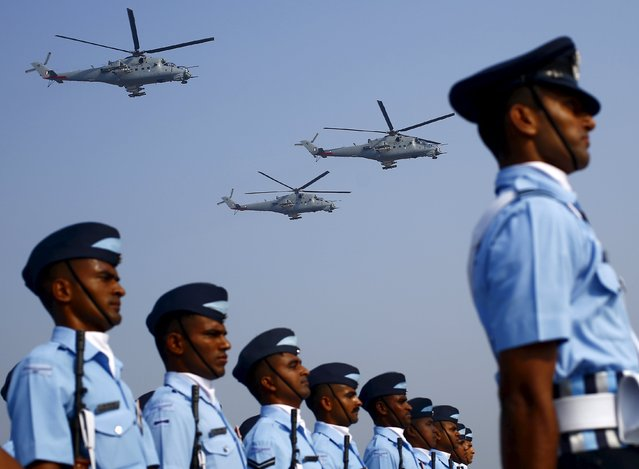 Indian Air Force soldiers march as Mil Mi-35 gunship helicopters fly during Indian Air Force Day celebrations at the Hindon air force station on the outskirts of New Delhi October 8, 2015. The Indian Air Force celebrated its 83rd anniversary on Thursday. (Photo by Anindito Mukherjee/Reuters)