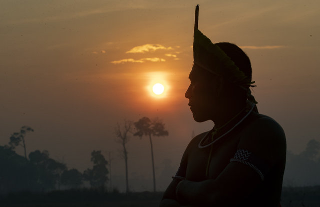 A Kayapo Indigenous man attends a protest at sunrise as they block highway BR-163 near Novo Progresso, Para state, Brazil, Monday, August 17, 2020. Dozens blocked the major highway in Brazil's Amazon on Monday to pressure the government for help in protecting them from COVID-19. (Photo by Andre Penner/AP Photo)