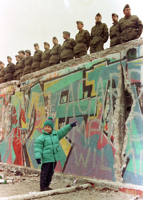 A young West German girl smiles at her father as she points to a large hole in the Berlin Wall, November 11, 1989. (Photo by Reuters/Stringer)