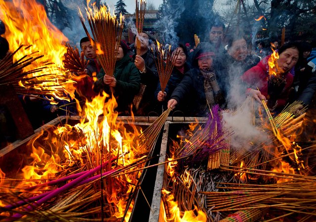 Temple goers burn incense as they pray for health and fortune on the first day of the Chinese Lunar New Year at Yonghegong Lama Temple in Beijing, on February 10, 2013. Millions across China are celebrating the arrival of the Lunar New Year, the Year of the Snake, marked with a week-long Spring Festival holiday. (Photo by Andy Wong/Associated Press)