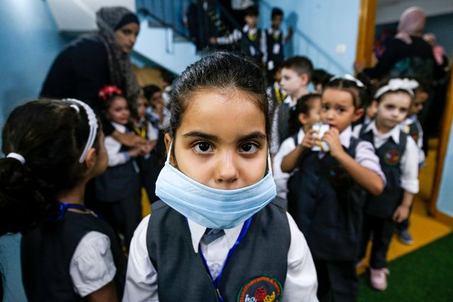 A girl clad in mask poses for a picture during an awareness session about COVID-19 coronavirus disease held by a local kindergarten in Gaza City on August 10, 2020, as education facilities in the Palestinian enclave re-opened for the new 2020-2021 academic year following an easing of pandemic restrictions. (Photo by Mohammed Abed/AFP Photo)