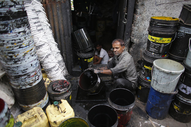 A worker cleans a used paint bucket at a recycling factory in Mumbai June 3, 2013. (Photo by Danish Siddiqui/Reuters)