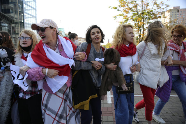 Women wearing old Belarusian national flags attend an opposition rally to protest the official presidential election results in Minsk, Belarus, Saturday, September 19, 2020. Daily protests calling for the authoritarian president's resignation are now in their second month and opposition determination appears strong despite the detention of protest leaders. (Photo by TUT.by via AP Photo)