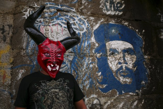 "A man dressed as a devil poses next to a grafitti of late rebel hero Ernesto ""Che"" Guevara in the indigenous community of Monimbo in Masaya, Nicaragua, October 16, 2015. (Photo by Oswaldo Rivas/Reuters)"